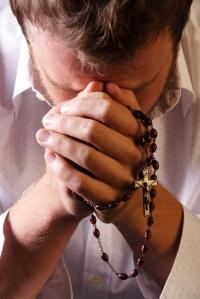man-praying-with-rosary