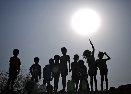 Children with their containers are silhouetted against the sun as they wait to fill drinking water from a water tanker provided by the state-run Delhi Jal (water) Board on a hot summer day in New Delhi, India, May 11, 2015. Temperature in Delhi on Monday reached 42.3 degree Celsius (108.14 degree Fahrenheit), according to India's metrological department website. REUTERS/Anindito Mukherjee - RTX1CFYJ