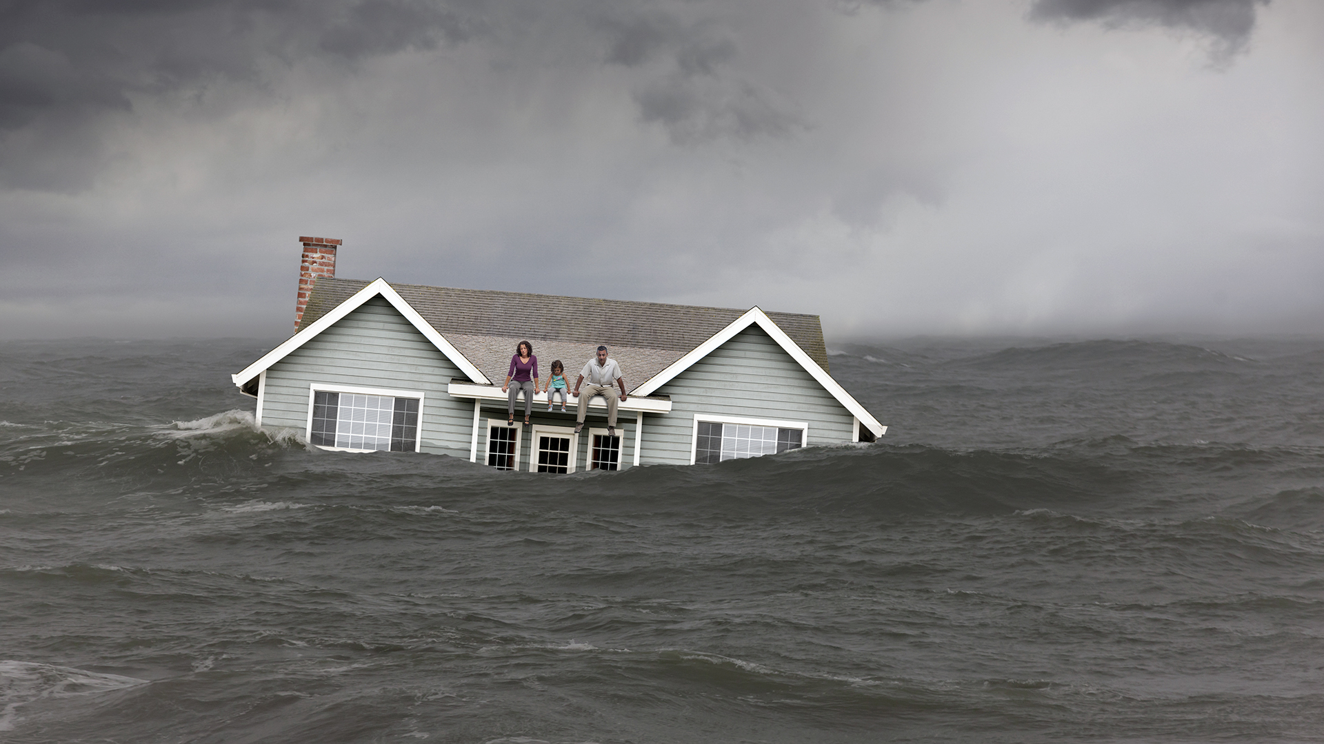 Family sitting on roof of house floating in sea