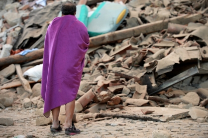 A man stands among the rubble of a house after a strong earthquake hit Amatrice on August 24, 2016. Central Italy was struck by a powerful, 6.2-magnitude earthquake in the early hours, which has killed at least three people and devastated dozens of mountain villages. Numerous buildings had collapsed in communities close to the epicenter of the quake near the town of Norcia in the region of Umbria, witnesses told Italian media, with an increase in the death toll highly likely. / AFP PHOTO / FILIPPO MONTEFORTE