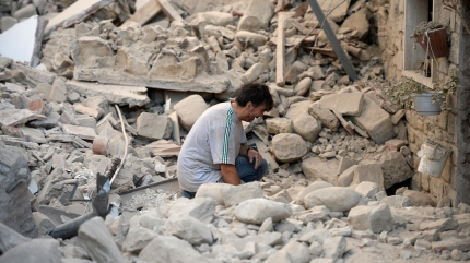 A man reacts to his damaged home after a strong earthquake hit Amatrice on August 24, 2016. Central Italy was struck by a powerful, 6.2-magnitude earthquake in the early hours, which has killed at least three people and devastated dozens of mountain villages. Numerous buildings had collapsed in communities close to the epicenter of the quake near the town of Norcia in the region of Umbria, witnesses told Italian media, with an increase in the death toll highly likely. / AFP PHOTO / FILIPPO MONTEFORTE