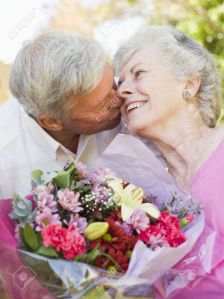 amor matrimonio -el-marido-esposa-flores-dando-besos-al-aire-libre-y-sonriente-foto-de-archivo