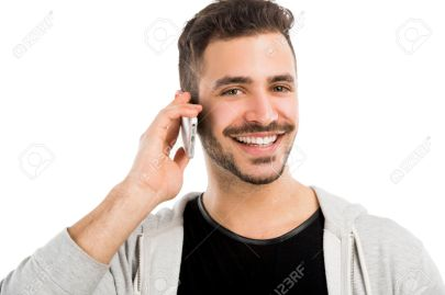 Portrait of a happy young man talking on cell phone isolated on white background